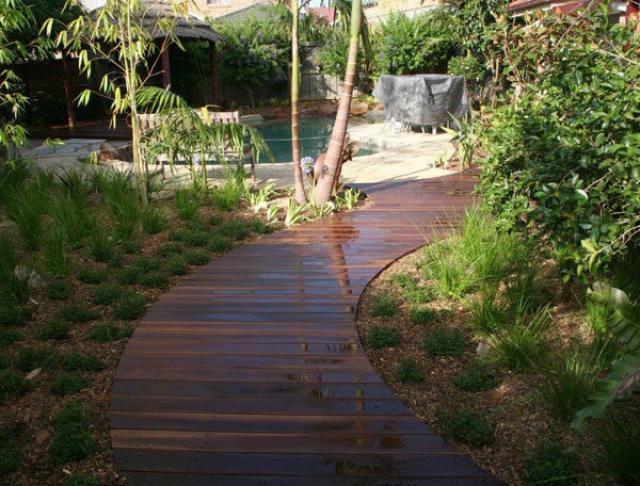 Уложенная деревянная дорожка на одном уровне с землей